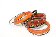 Juego de 7 pulseras de aro color naranja: 3 de madera con tachuelas y 4 metálicas labradas estilo dorado envejecido.    Medidas diámetro 7 cm  Ref.: AG7450E  http://www.meigallo.com/articulo/704/set-de-pulseras-rigidas