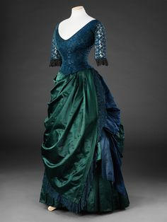 Blue and green silk satin evening or dinner dress with silk brocade bodice and blue cotton lace sleeves with black cotton ruffles. Drapery around skirt is edged with matching dyed cotton lace. Circa mid.1880s