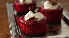 mini red velvet cheesecakes that are garnished with chocolate curls.