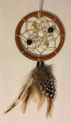 Suede-wrapped dreamcatcher necklace with wooden bead and neutral feather accents.