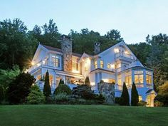 Beautiful, big farmhome with lovely stone chimneys, lit with big windows in the twilight.