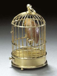 A JEWELLED GOLD AND SILVER-GILT MODEL OF AN OWL IN A CAGE  by Fabergé and with the workmaster's mark of Michael Perchin, St. Petersburg, 1899-1908, with scratched inventory number 8800 or 2800 Realistically carved, with diamond eyes and silver-gilt claws, in a silver-gilt cage with drawer and door and containing a water dish and a dish containing seed pearl, marked underneath and on the side of the tray