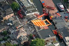 Dramatic moment homes and shops are demolished when two cranes collapse while moving a section of bridge in Holland