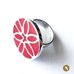 Anillo de plata, en la circunferencia se puede apreciar una forma de flor construida en plata y todo cubierto por una resina pigmentada roja.  Autor:Monoco Colección: FLOWER POWER Materiales: Plata Dimensiones:N° 18, figura de 3 cm de diámetro Pieza única: Sí