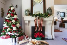 Striped wool Christmas stockings from Cranfields hang from the fireplace mantel in the formal lounge below a white hydrangea wreath; Jo has decked the tree in red and white silk hydrangeas, feather garlands, white and silver birds and red and silver baubles.