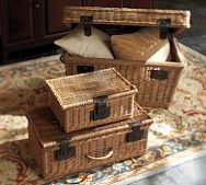 Collect various picnic baskets and use for storage, all stacked together.