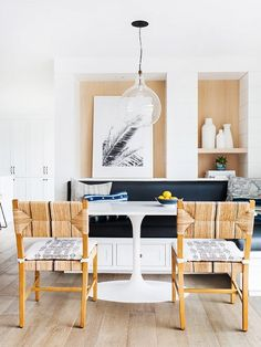 Bright, nautical inspired dining space with a blue bench and a low-hanging pendant light
