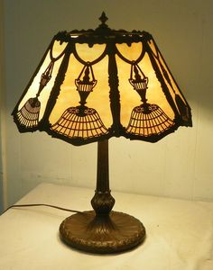 Antique lamp with eight caramel slag glass paneled sections & base of lamp nicely decorated with lily pad type design