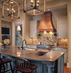 "Warm and Welcoming Georgia Kitchen - The warmth of a custom, copper hood took center stage in creating a welcoming ambiance, and the cabinetry finish was equally important in creating the look.  A mix of finishes were selected to impart a ""loved and lived in"" look.  Dura Supreme's hand-detailed finishes include a weathered finish for the bar area and a ""Heritage Paint"" finish for the kitchen perimeter. Kitchen design by Splash Kitchens & Baths in LaGrange, GA – Dura Supreme Blog"