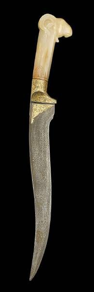 A Mughal-style jade-hilted steel Dagger & A Mughal-style rock crystal Dagger Hilt.  photo Bonhams.  With tapering and slightly curving watered steel blade with a flattened spine, the forte decorated in gold with foliate motifs, the light greenish-beige hilt carved in the form of a ram's head, slightly facetted - 48.2 cm. long