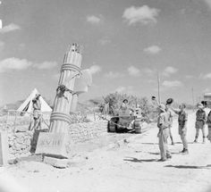 CAMPAIGN EAST AFRICA 1941 (E 2367)   British troops use a bulldozer to pull down a fascist stone monument at Kismayu in Italian Somaliland, 11 April 1941