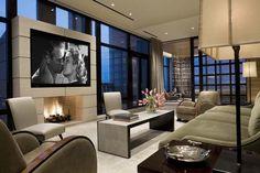 Spacieux et luxueux salon à l'ameublement design et à la télé au-dessus de la cheminée