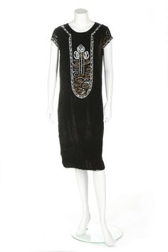 Jean Patou couture beaded velvet dress, circa 1925. A Jean Patou couture beaded velvet dress, circa 1925. narrow pink on white woven label, embroidered to the front with three tall blooms in a pool, worked in gilt and white beads and metal strip, similarly worked sleeves, bust 92cm, 36in This dress formed part of a wedding trousseau in 1925.. - See more at: http://kerrytaylorauctions.com/one-item/?id=82&sub=%20&auctionid=429#.dpuf