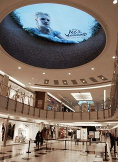 Disney's Alice in Wonderland digital signage in a mall in Rome.