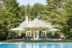 The poolhouse at Ricky and Ralph Lauren's Bedford, New York, estate is encircled by towering pines.