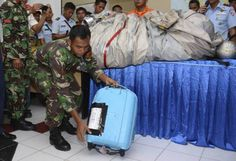An Indonesian Air Force personnel show a suitcase and airplane parts, on the table, recovered from the water near the site where AirAsia Flight 8501 disappeared, during a press conference at the airbase in Pangkalan Bun, Central Borneo, Indonesia, Tuesday, Dec. 30, 2014. Bodies and debris seen floating in Indonesian waters Tuesday, painfully ended the mystery of AirAsia Flight 8501, which crashed into the Java Sea and was lost to searchers for more than two days. (AP Photo/Dewi Nurcahyani)
