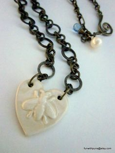 """$34.99 This one of a kind heart charm is embossed with a honeybee and was handmade, glazed and fired on the Isle of Wight. It is finished with a large saltwater pearl. Free US ship and 20% off with coupon code """"homecoming."""""""