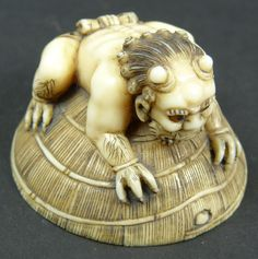 "19th C JAPANESE IVORY STUDY OF ONI ON SEDGE HAT Antique Japanese ivory okimono figure depicting oni demon resting on sedge hat. Hidden under the sedge hat is a katana sword. Finely carved with high attention to detail and having enamel inlayed eyes. Signed to bottom. Measures approx. 3"" height x 3"" width"