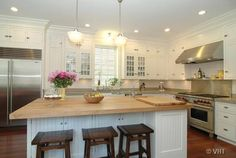 kitchens - walnut stools butcher block island countertop white beadboard white kitchen glass front cabinets subway tiles stainless steel appliances kitchen Schoolhouse Pendant