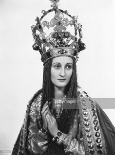 English stage and film actress Joyce Bland (1909 - 1963), wearing an elaborate costume and bejewelled crown resembling the Madonna's. The costume is for a performance of 'The Marvellous Life of St Bernard' at the Malvern Festival, Hereford and Worcester.