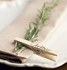 Marcadores de lugar feitos com um raminho de erva aromática, prendedor comum de madeira e caneta com tinta dourada.