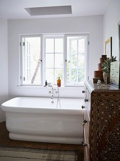 With its Indian inlaid bureau, vintage Moroccan rug, shell artwork, and tigerwood set of miniature drawers, this bathroom has some serious bohemian vibes.