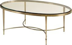 The Oval Coffee Table features a clear glass, beveled top that sits slightly raised from its surrounding, sleek metal apron. The table is supported by four straight, gently tapered metal legs joined in an interlocking, half-moon stretcher.