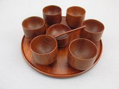 Simple but elegant 6 wooden egg cups, salt cup and a tray. Made of teak wood in the 60´s, probably in Denmark.  Very good condition.  m e a s u r e m e n t s Cups: 4 cm / 1,6 x 5 cm / 2 Weight: 360 g   We shipp this item uninsured, it means that we are not liable for demages or getting lost. Should you wish an insured shipping, please choose this option additionally. Vintage West German Mid Century houseware kitchenware.  Feel free to ask me any questions! Combined shipping is possible, see…