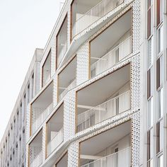 Angular balconies extending from the front of this apartment block in Paris are framed by white concrete screens featuring a perforated pattern that resembles brickwork. Read the full story on dezeen.com/architecture  #architecture #paris
