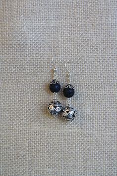 These dangle earrings feature a round lava stone bead and an antiqued silver plated bead which together create a stunning set of earrings. A lovely scrolled bead cap sits atop the lava stone bead which combined with the silver plated bead create a nice antique yet contemporary