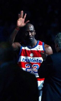 Michael Jordan in a Washington Bullets (now Wizards) jersey waves goodbye to his fans after his final home game against the New York Knicks at the MCI Center.