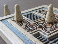 """Knossos game is the ancient board game discovered by Evans in the Palace of Knossos and goes back to 1600 BC. It is a """"race game"""", but at the same time something more. It portrays an ancient symbolism about life and the trip to Hades with a return back to life. A gap between the two parts of the board is supposed to represent the River-Ocean that separates the world of the living from the world of the dead."""