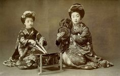 Playing the Taiko and the Kotsuzumi 1910s. A very young, Maiko Tomigiku playing the Taiko (large drum), with a more senior Maiko Manryu playing the Kotsuzumi (small drum kept at the right shoulder). This postcard must date to 1912 or earlier, as Manryu was a Geiko (Geisha) by 1913.