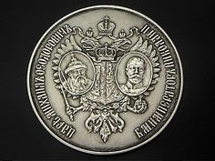 "Obverse side of the Tercenteniary Silver school prize medal 1913, with the portraits of Tsars Michael and Nicholas II, and the coat of arms of the House of Romanov laid on double headed Imperial eagle, for those who graduated with honors in the year of the 300th anniversary of the Romanov dynasty. Diameter 1 11/16 in (42 mm).  Scarce one year type medal.  Reverse with the dates 1613-1913 and a scroll with Cyrillic inscription ""successful""."