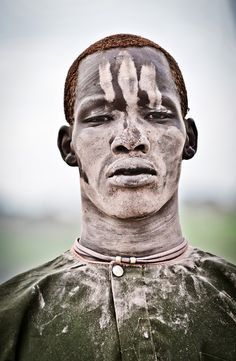 Africa | A Mundari male covered in ash and orange hair bleached in the sun from washing it in cow urine. Terekeka, Bahr al Jabal, Sudan | ©Tom McShane