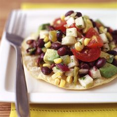 Mexican Black Bean Salad Tostada - This Mexican specialty features jicama, avocado, corn and lime juice, tossed together and piled up high on top of crunchy tortillas! 4 SmartPoints
