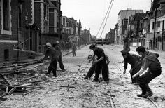 Saint-Malo. August 8-10, 1944. French civilians clear rubble as American troops march through the streets//Robert Capa