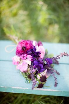 Bouquet designed with sweet pea, ranunculus, scabiosa, and blooming oregano.  Purple flowers with yellow dress.