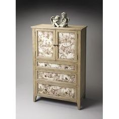 """Artfully handcrafted, this beautiful chest offers three English dovetail drawers and a top storage cupboard. The weathered driftwood finish and toile-print panels pair perfectly for heirloom appeal.         Product: ChestConstruction Material: Gemelina wood solids, maple veneers and fabricColor: DriftwoodFeatures:  HandcraftedEnglish dovetail drawersThree drawers Dimensions: 58"""" H x 37"""" W x 22"""" D"""