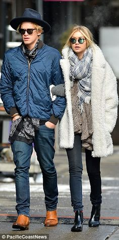 Rugging up! Gigi kept warm in a white furry coat, with a large checked scarf over a brown jumper, blue skinny jeans and black booties