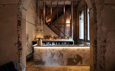 Beta Bar Sydney. raw brickwork and elegant arches with metallic accents and muted tones, creating an elegant modern space within the original, organic environment.