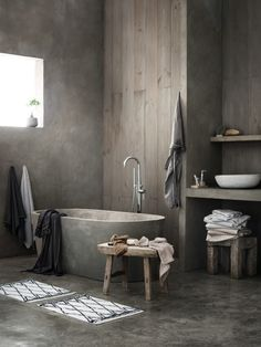 Bathroom in shades of grey, concrete and wood. Beautiful styling and H&M home towles.