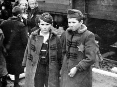 """Two Jewish brothers, wearing military-style forage caps and elaborate overcoats, arrive at Auschwitz. They cannot foresee what awaits them. Young enough to be """"ineligible"""" for hard labor, they were almost certainly sent to the gas chamber within hours after the photographer snapped this photo."""