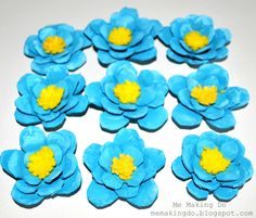 more flowers with the egg carton      Cut slits and round them to make a flower shape      Paint them with craft paints and stack and glue them together. (I used 2 colors of blue craft paint to make them look more realistic).      Cut a scrap piece of felt you have leftover from another project. This will be be pretty small, for the center of the flower.      cut little slits along one side      Roll up the felt and glue to the middle of your flower and your done!