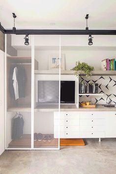 Decoração de apartamento pequeno com cimento queimado e tons neutros. Na cozinha, armário branco, plantas, prateleira com livros, plantas e quadro.    #decoracao #decor #details #casadevalentina