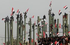 Supporters of anti-US Shi'ite cleric Moqtada al-Sadr wave Iraqi flags during a rally in Baghdad. (Reuters)