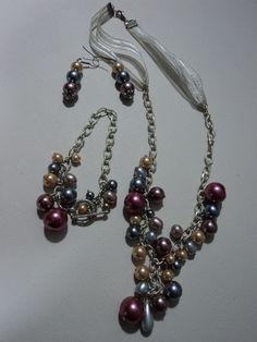 Moderno collar de 70 cm de largo con pulsera, elaborados en perlas de cristal en tres diferentes tamaños y ganchos de plata.