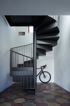 A spiral iron staircase curves above a tiled floor.