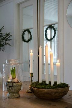 Christmas wreaths and candles at different heights in moss- Kerstkransen en k.