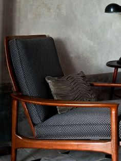 Lizzo -  Arizona Fabric Collection - Stained wood chair with thin black seat cushions covered in tiny grey dots, with a wavy striped textured cushion and black anglepoise lamp